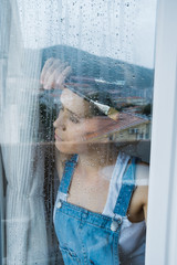 In search of inspiration. Sad young woman painter looks out the window at the rain