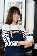 Young asia woman barista holding a disposable coffee cup with smiling face at cafe counter background, small business owner, food and drink industry