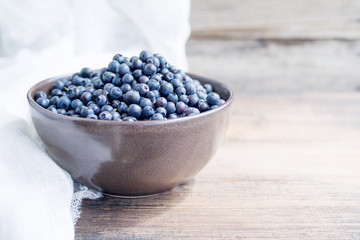 Summer wild berry fresh blueberries in a cup on a wooden background closeup.