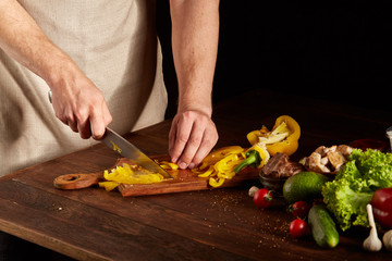 Chef's hands cutting yellow bell pepper for colorful barbecue composition on wooden table, close-up, selective focus.
