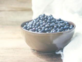 Fresh blueberries in a cup on a wooden background closeup. Summer wild berry