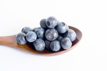 Fresh blueberries in a wooden spoon on a white background closeup