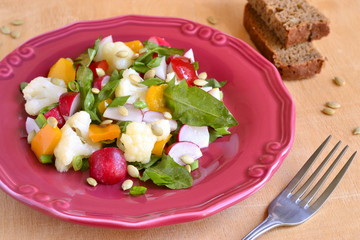Salad with cauliflower, radish, sweet pepper and greens