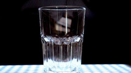 Ice in a transparent glass, black background.