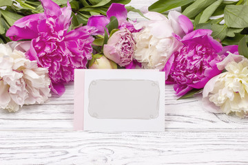 Peony flowers border blank greeting card white wooden background.
