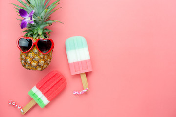 Table top view aerial image of summer & travel beach holiday in the season background concept.Flat lay sign objects food on season for travel.pineapple wear sunglasses with ice cream on pink paper.
