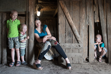 Slender girl is posing in old wooden barn with motley chicken and her children. Natural scenes of peasant life. Country's vacation. Fresh air, natural organic food, childhood in village