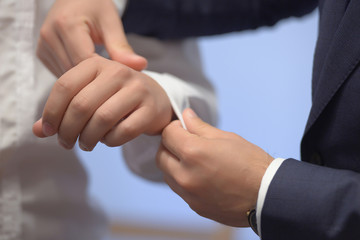 Close-up shot of hands of young white Caucasian male being helped with his white shirt by another elegantly dressed man. Classy groom, stylish businessman, or millennial male model getting ready.