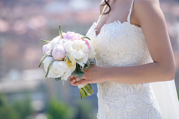 Profile view of a young Caucasian bride wearing an embroidered wedding dress and holding a round peonies bouquet, an essential accessory for the perfect, romantic look