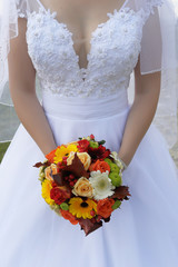 Young Caucasian bride wearing a lacy wedding dress and holding a round  and vibrant summer flowers bouquet in front, an essential accessory for the bride's big day