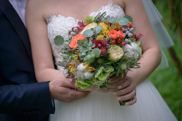 Cropped shot of young Caucasian couple with bride holding a large  autumn flowers bouquet with succulents and berries, a colorful accessory for the wedding day, and groom gently holding her arm