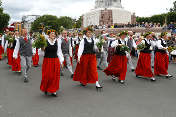 People wear traditional dress as they walk in Song and Dance Celebration procession throughout the streets of Riga