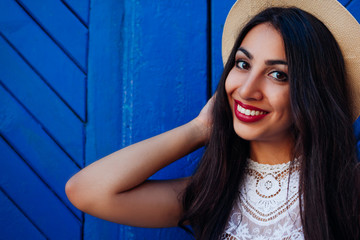 Happy middle-eastern girl smiling and looking at camera. Outdoor portrait of young woman wearing summer hat
