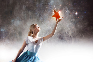 Young attractive woman reaching for the star. Take a star from the sky, dreams and plans, concept