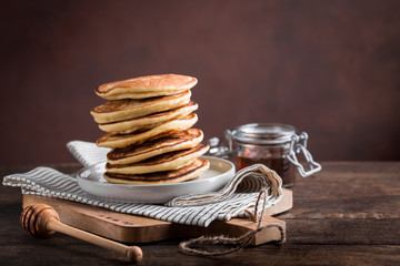 Stack of homemade pancakes with honey on rustic wooden background, copy space