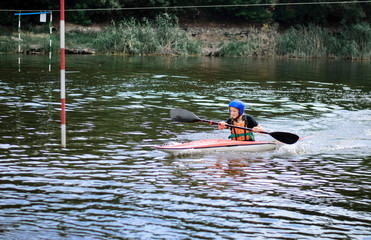 young teenager girl actively manages a sports kayak boat on a beautiful river