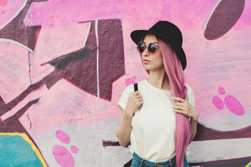 Beautiful stylish young hipster woman with long pink hair, hat and sunglasses on the street.