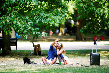 People relax in the sunshine at Green Park in London
