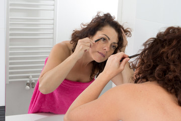 woman in her bathroom facing the mirror and putting on make-up on her eyes