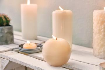 Many burning candles on wooden shelf