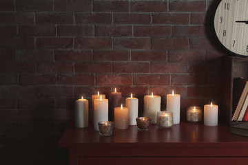 Many burning candles on wooden table against brick wall
