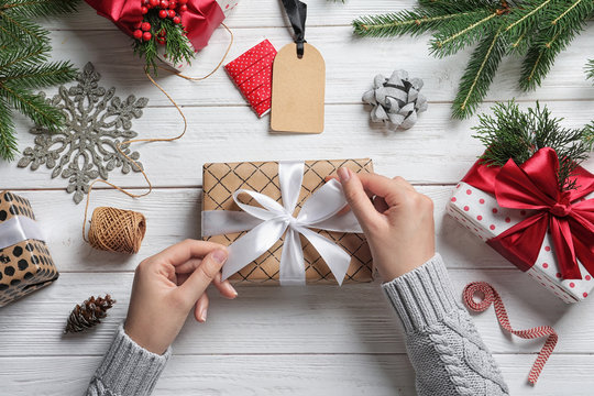 Woman wrapping Christmas gift at wooden table, top view
