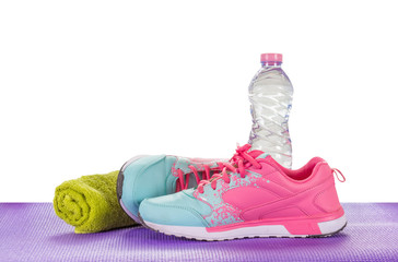 Women's Sports Shoes, Water Bottles, Towels on a fitness pad ,isoalted on white ackground with clipping path.