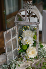 Old, vintage candle cage or lantern repurposed as a rustic, shabby chic wedding decor with white flowers and greenery accents, for guests dinner tables as centerpiece or as interior decoration