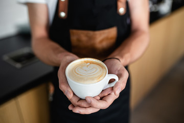 Professional barista holding cup of espresso coffee with milk.