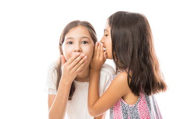 Younger sister whispering news to older sister's ear