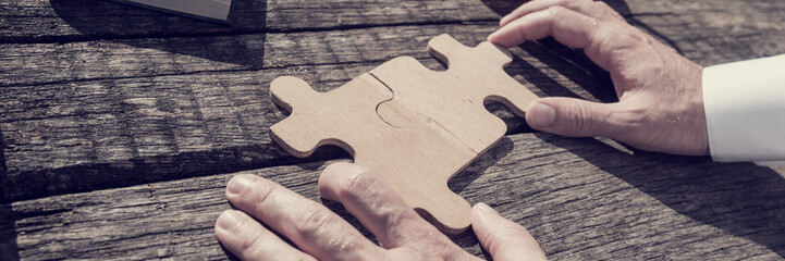 Wide close up on unidentifiable business person with hands putting together two puzzle pieces