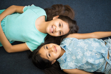 Happy sisters lying on floor with head to head