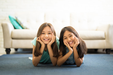 Portrait of two sisters lying on the floor in living room smiling