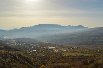 soft rays of the midday sun illuminate the autumn valley. a small village surrounded by mountains.