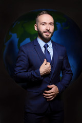 Portrait of a serious man in a suit and tie businessman boss on a dark background of the globe Earth