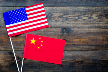 USA-China relations. Country cooperation. American and Chinese flags on dark wooden background top view copy space