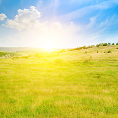 Hilly green fields and sunrise on a blue sky.