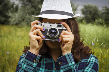 A young girl in a white hat is holding an old camera