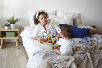 Indoor shot of beautiful young mixed race female wearing jeans, white shirt and headband lying on bed, playing with her 1 year old baby boy in modern light bedroom interior. Motherhood and childcare