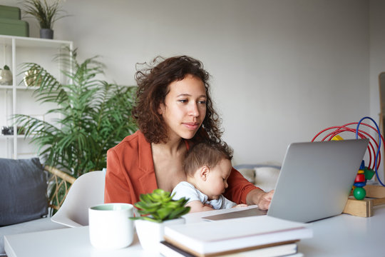 Motherhood, career and employment concept. Casually dressed young dark skinned single mother nursing baby and looking for job online, browsing websites, sitting at desk in front of open laptop