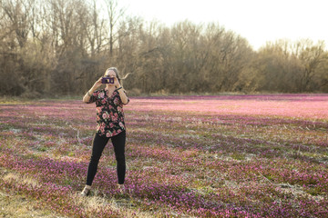 Woman taking phone picture standing in a field of early spring flowers against a blurred background
