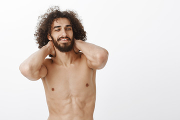Waist-up shot of good-looking confident curly-haired guy with beard, holding hands behind neck and smiling pleased and joyful. waking up after great night with girlfriend, being satisfied and relaxed