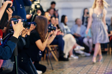Closeup of photographers working on presentation of modern fashion show