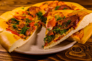 Ceramic plate with sliced homemade pizza on a wooden table