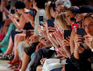 Guests take pictures with their phones as model presents a creation by designer Maxime Simoens as part of his Haute Couture Fall-Winter 2018/2019 fashion show for fashion house Azzaro Couture in Paris
