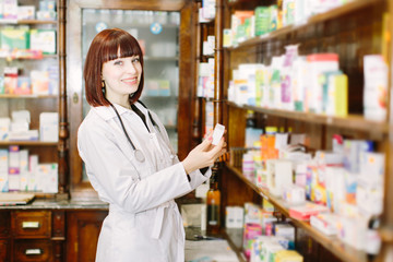 Perfect medication. Shot of a young beautiful pharmacist looking for an ordered drug on a shelf at the local pharmacy.