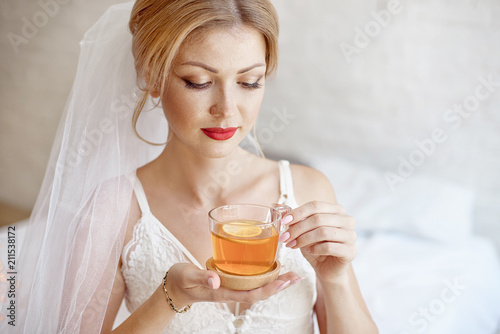 af9aa0d0ae9 Close-up blonde bride drinking morning tea in lingerie and veil ...