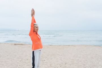 Fit woman doing stretching exercises on a beach