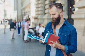 Attractive bearded tourist standing in a street