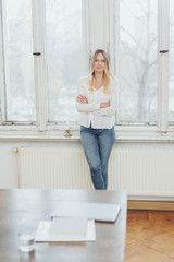 Blonde woman standing by window at home